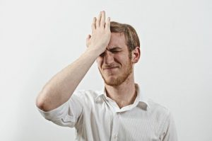 Frustrated young man holding head in his hands