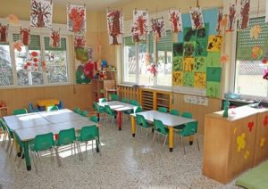 classroom with children's paintings hanging from the ceiling